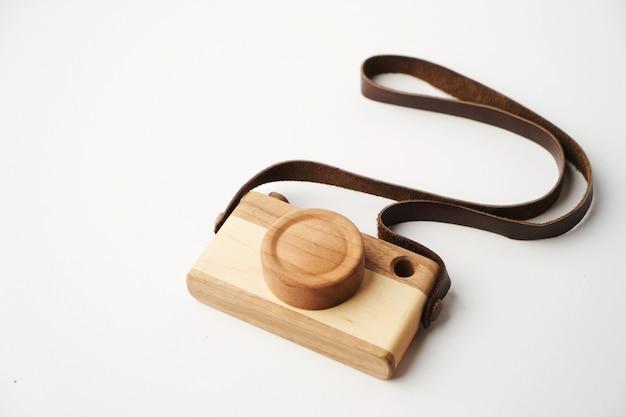 Baby speelgoed fotocamera op een wit oppervlak met kopieerruimte. houten cameraspeelgoed met leren riem