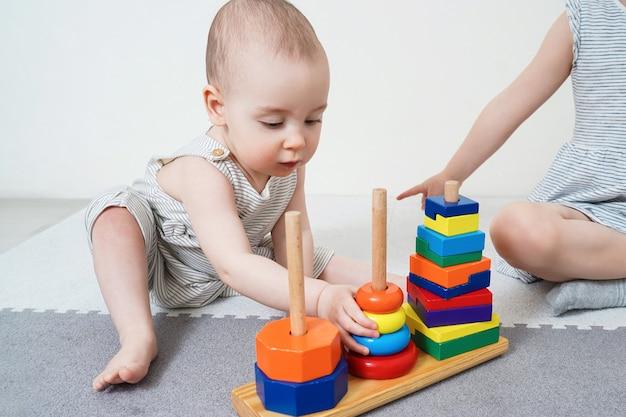 Baby speelt met een piramide. meisje leert een piramide samen te stellen. vroege ontwikkeling van kinderen tot een jaar oud.