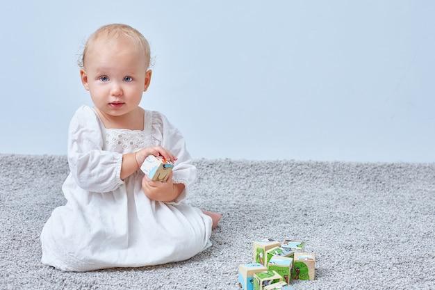 Baby speelt met houten blokjes op een lichte achtergrond met copyspace. opvoeding en ontwikkeling van kinderen.