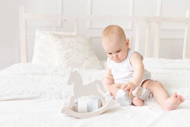 Baby speelt met houten speelgoedblokjes op het bed in een lichte kamer