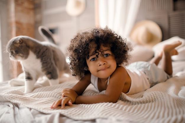 Baby speelt met kat thuis op het bed
