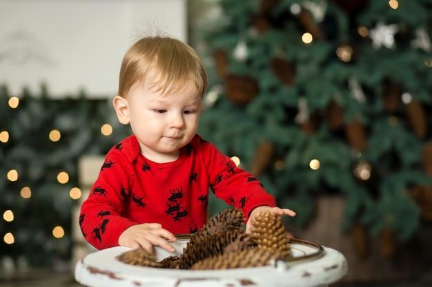 Baby speelt met kegels om de kerstboom te versieren.