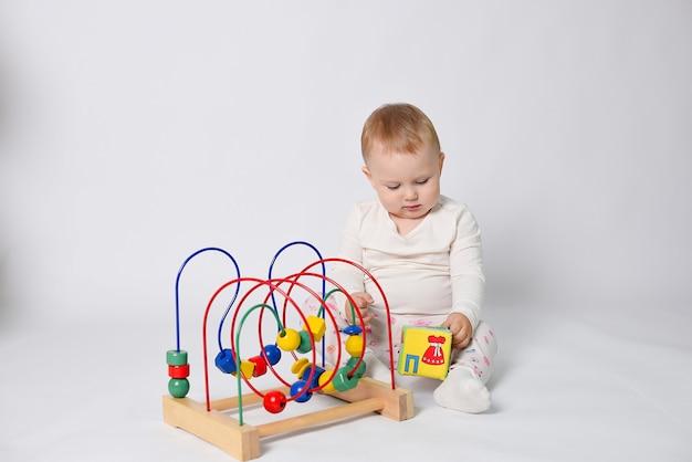 Baby speelt met zachte blokken een kind op een witte achtergrond zit in lichte kleren, speelt met speelgoed en lacht