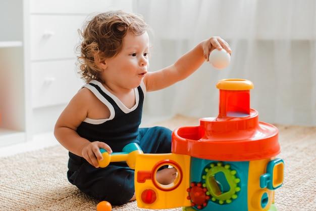 Baby speelt op de vloer in de kamer in educatief plastic speelgoed.