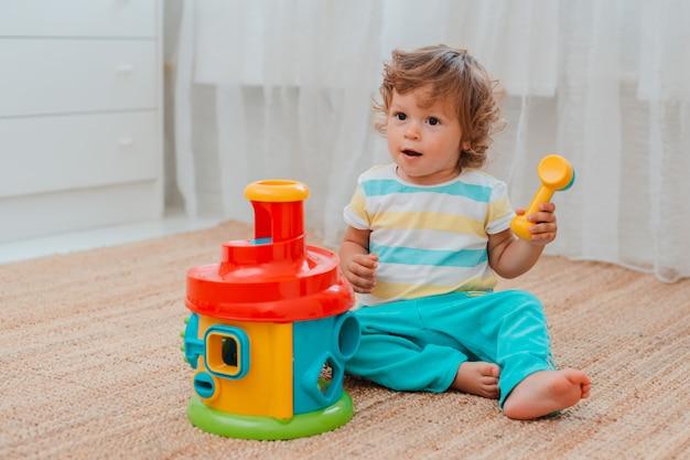 Baby speelt op de vloer kamer met educatief plastic speelgoed.