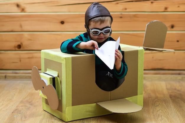 Baby spelen in kartonnen vliegtuig kindertijd piloot reizen vliegveld verbeelding kind piloot school innovatie droom kinderen en avontuur