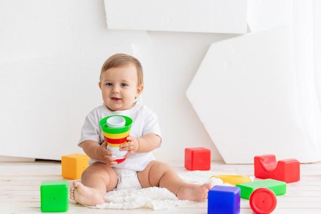 Baby spelen met gekleurde blokjes in een lichte kamer thuis