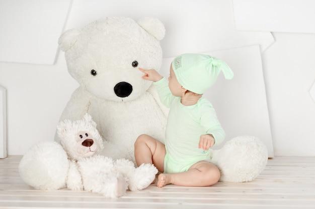 Baby spelen met grote teddybeer thuis in lichte kamer, spel en vrijetijdsbesteding voor kinderen concept