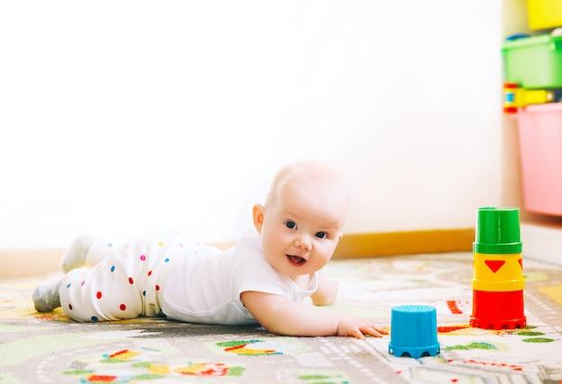 Baby spelen met kleurrijk speelgoed thuis gelukkig 6 maanden oud baby kind spelen en ontdekken