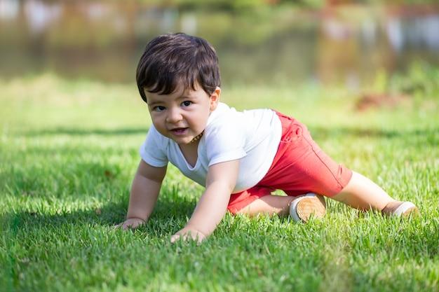 Baby spelen op het gras in een park.