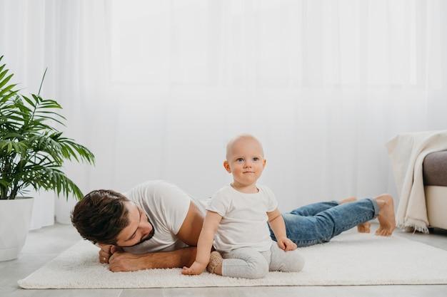 Baby staande op de vloer thuis met vader