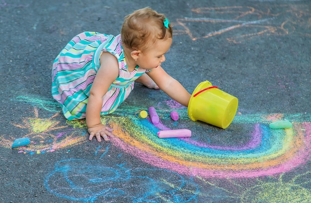 Baby tekent een regenboog op de stoep met krijt. selectieve aandacht. natuur.
