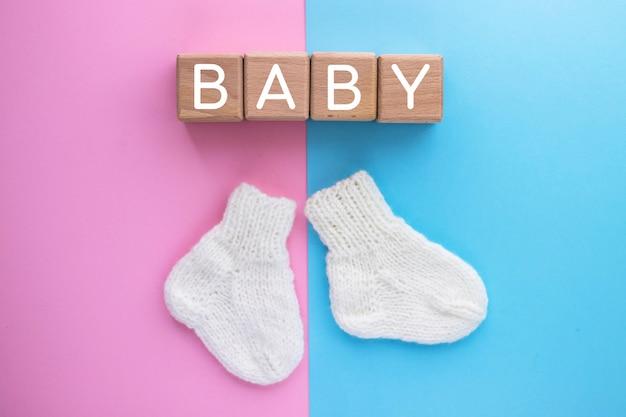 Baby tekst op houten blokjes en paar schattige gebreide sokken op roze-blauw