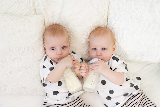 Baby-tweelingen liggen in hun pyjama op het bed en drinken melk uit flessen