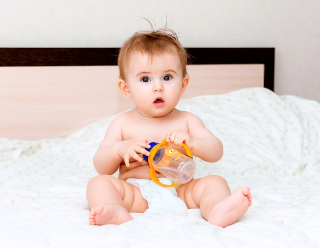 Baby van 6 maanden oud drinkt water uit een fles, liggend op het bed. blije en blije baby