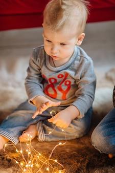 Baby van één jaar poseert voor een fotograaf in een nieuwjaarsinterieur