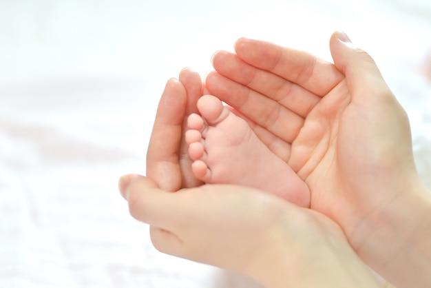 Baby voeten in de handen van de moeder.