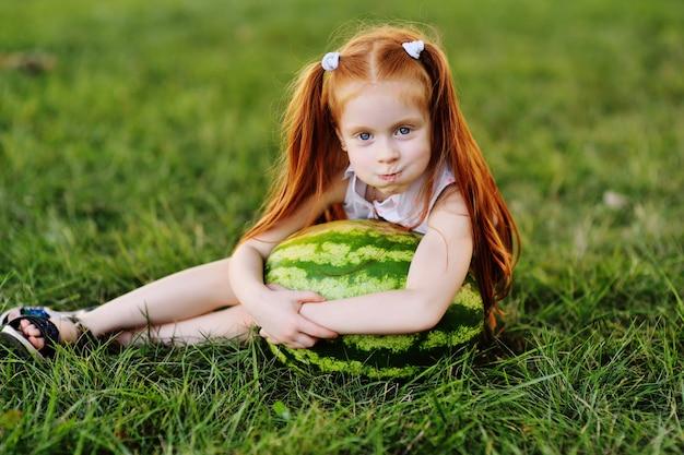 Baby weinig grappig meisje met rood haar die op een reusachtige watermeloen in het park op het gras op een de zomerdag leunen