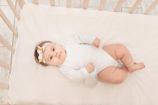 Baby zes maanden in bed met een fles water in een witte bodysuit