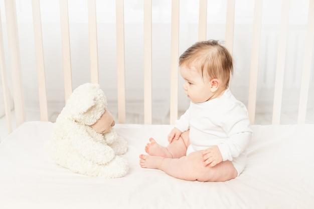 Baby zes maanden spelen in een wieg in een wit rompertje met een teddybeer