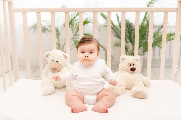 Baby zes maanden zittend in een wieg in een wit romper met speelgoed teddyberen