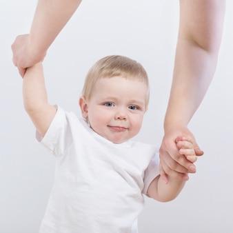 Baby zet eerste stappen met de hand van mama