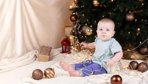 Baby zit bij een kerstboom en speelt met een slinger waarin hij verstrikt is, speelgoedballen liggen rond.