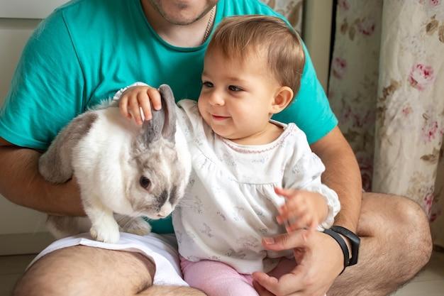 Baby zit in vaders armen en aait een decoratief konijn als huisdieren in een gezin met kinderen
