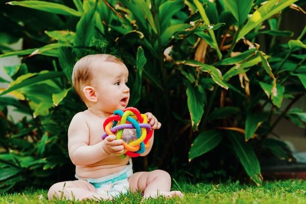 Baby zittend op het blote voeten gazon spelen met een kleurrijke speelgoed om zijn zintuigen te stimuleren.