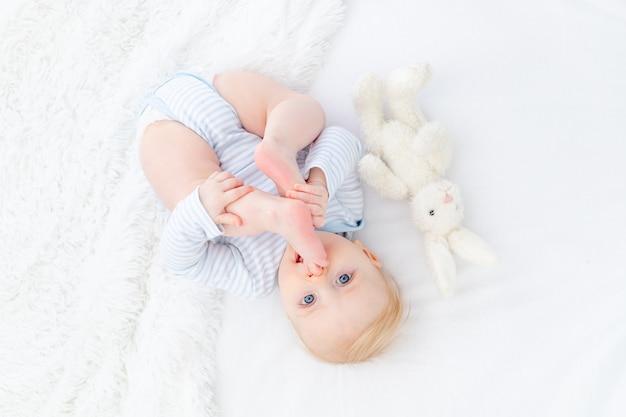 Baby zuigen voet liggend op bed, babyjongen blonde zes maanden