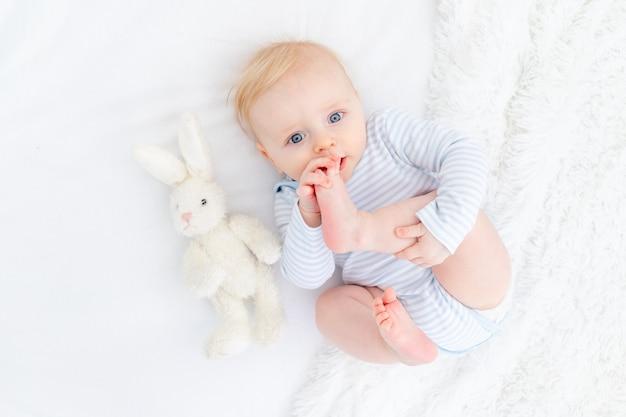 Baby zuigende voet liggend op bed, babyjongen blond zes maanden