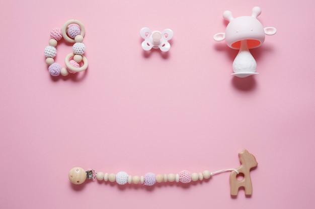 Babyaccessoires concept: bijtring, rups speelgoed en babyfopspeen, over roze achtergrond met kopie ruimte, bovenaanzicht, plat lag