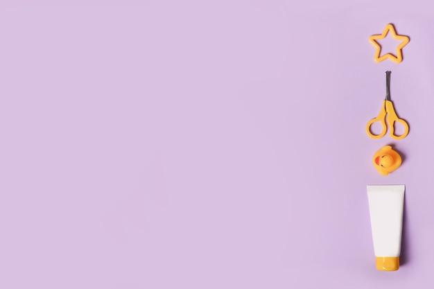 Babyaccessoires voor bad met eend op paarse achtergrond. kopieer ruimte