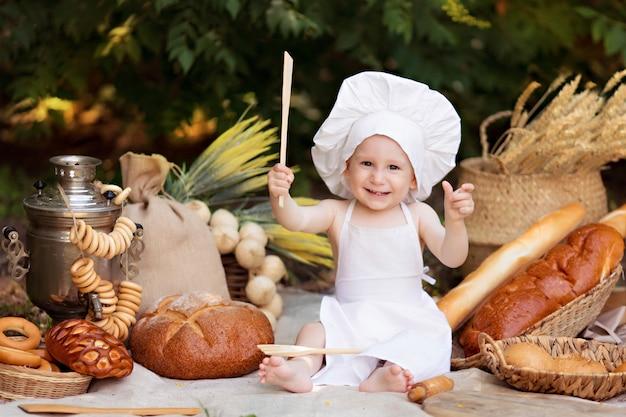 Babybakker kookt in de natuur. jongen op een picknick eet brood en bagels in een witte schort en hoed