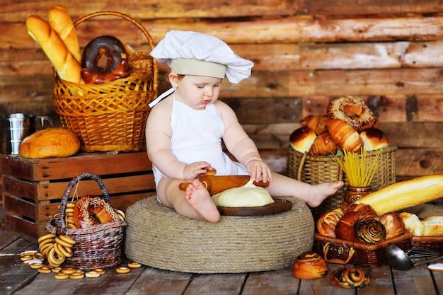 Babybakkersjongen in een koksmuts en schort rolt rauw deeg uit met een houten deegroller tegen de achtergrond van bakkerijproducten