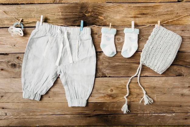 Babybroek; sokken; hoofddeksel en fopspeen opknoping op waslijn met wasknijpers tegen houten muur