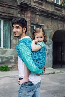Babydragend en mobiel modern ouderschap van vader en babymeisje in draagdoek