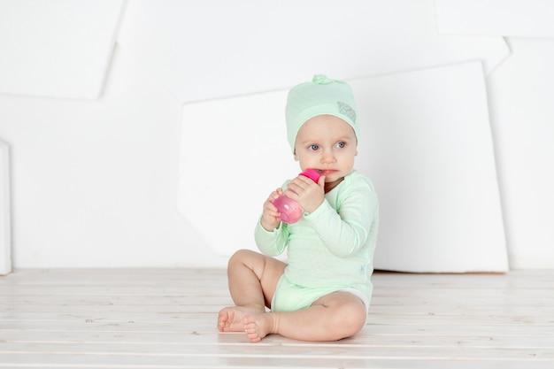 Babydranken uit een flesje in een groene bodysuit, het concept van voeding en babyvoeding