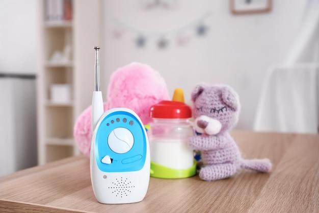 Babyfoon, drinkbeker en speelgoed op tafel in de kamer. radio oppas