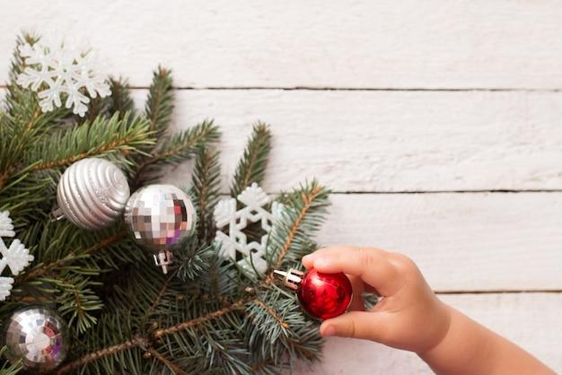 Babyhand en kerstboom met decor op witte houten achtergrond, kopieer ruimte. winter kind vakantie