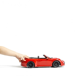 Babyhanden die rode stuk speelgoed auto houden die op witte achtergrond wordt geïsoleerd. ruimte kopiëren