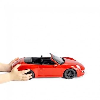 Babyhanden die rode stuk speelgoed auto houden die op witte achtergrond wordt geïsoleerd