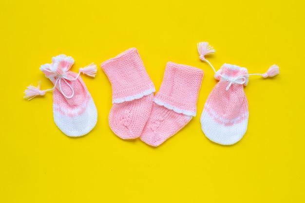 Babyhandschoenen en sokken op gele achtergrond.