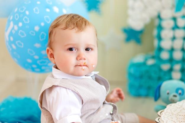 Babyjongen 1 jaar in een fotostudio met een cake en ballonnen, verjaardag van een kind 1 jaar, baby eet cake