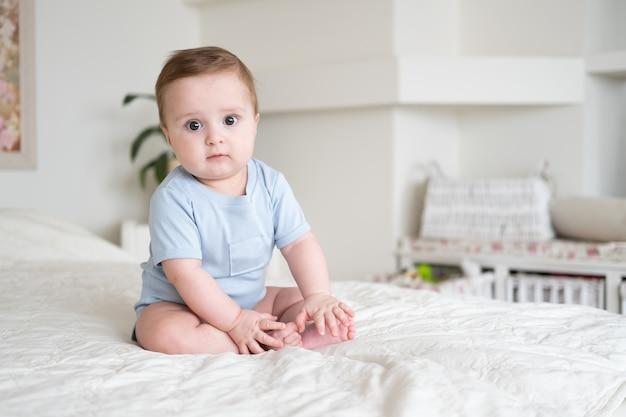 Babyjongen 6 maanden oud in blu romper glimlachend en zittend op wit bed thuis.