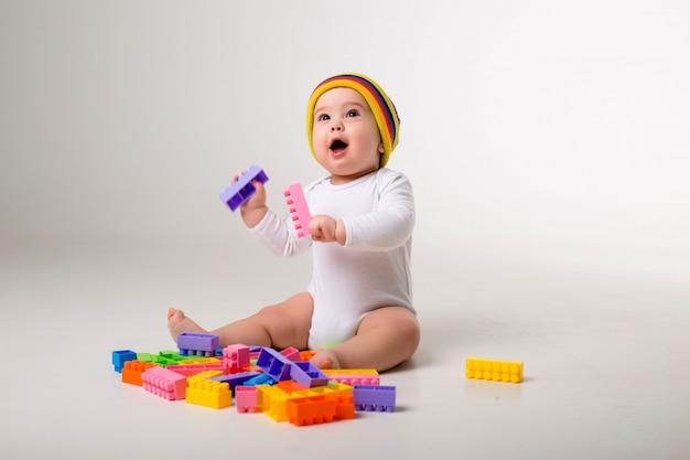 Babyjongen 9 maanden oud spelen met een veelkleurige aannemer op een witte muur