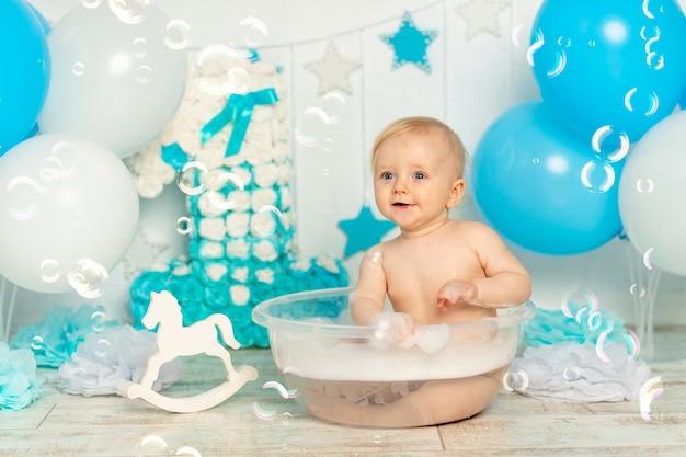 Babyjongen baadt in een bad met zeepbellen en schuim in een feestelijk verjaardagsdecor een jaar oud in blauw met ballonnen, vakantie en decorconcept