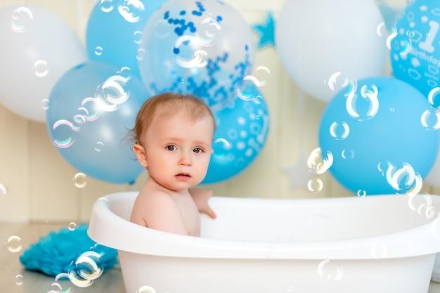 Babyjongen baadt in een badkuip met ballonnen en zeepbellen, gelukkige jeugd, verjaardag van kinderen