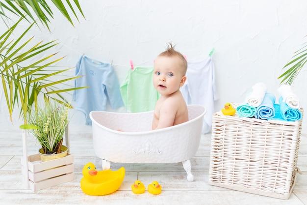 Babyjongen baadt in een badkuip met een rubberen eend, het concept van hygiëne en wassen