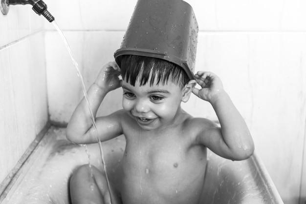 Babyjongen badend in de gootsteen